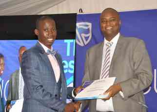 Stanbic Chief Executive Patrick Mweheire hands over a certificate to one of the entrepreneurs who completed training at the Stanbic Bank Incubator