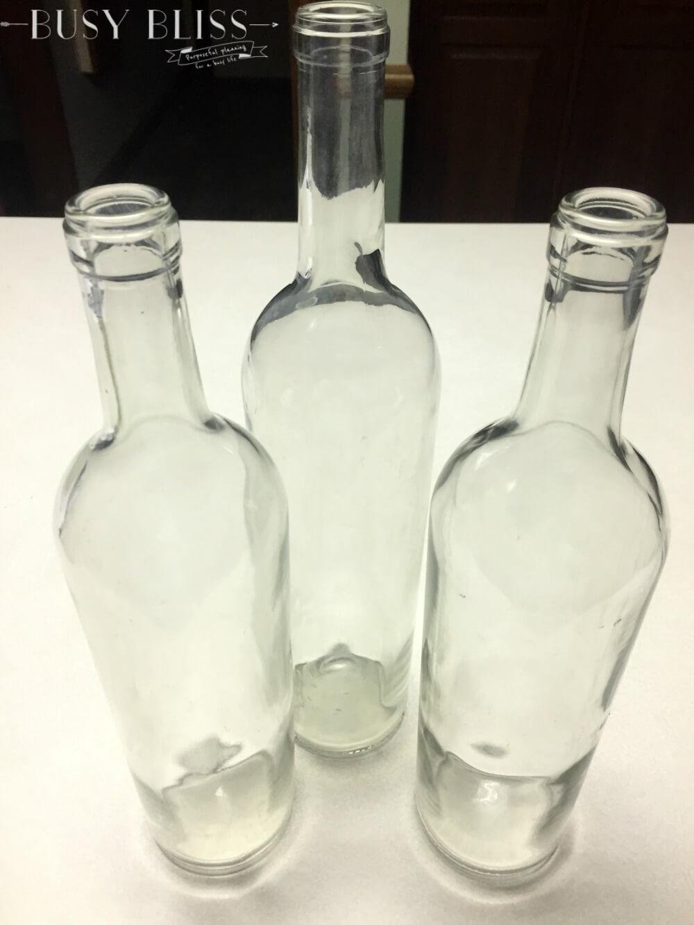 The simple way to make decorative wine bottles with a hot glue gun and spray paint. This project can be done in about an hour!