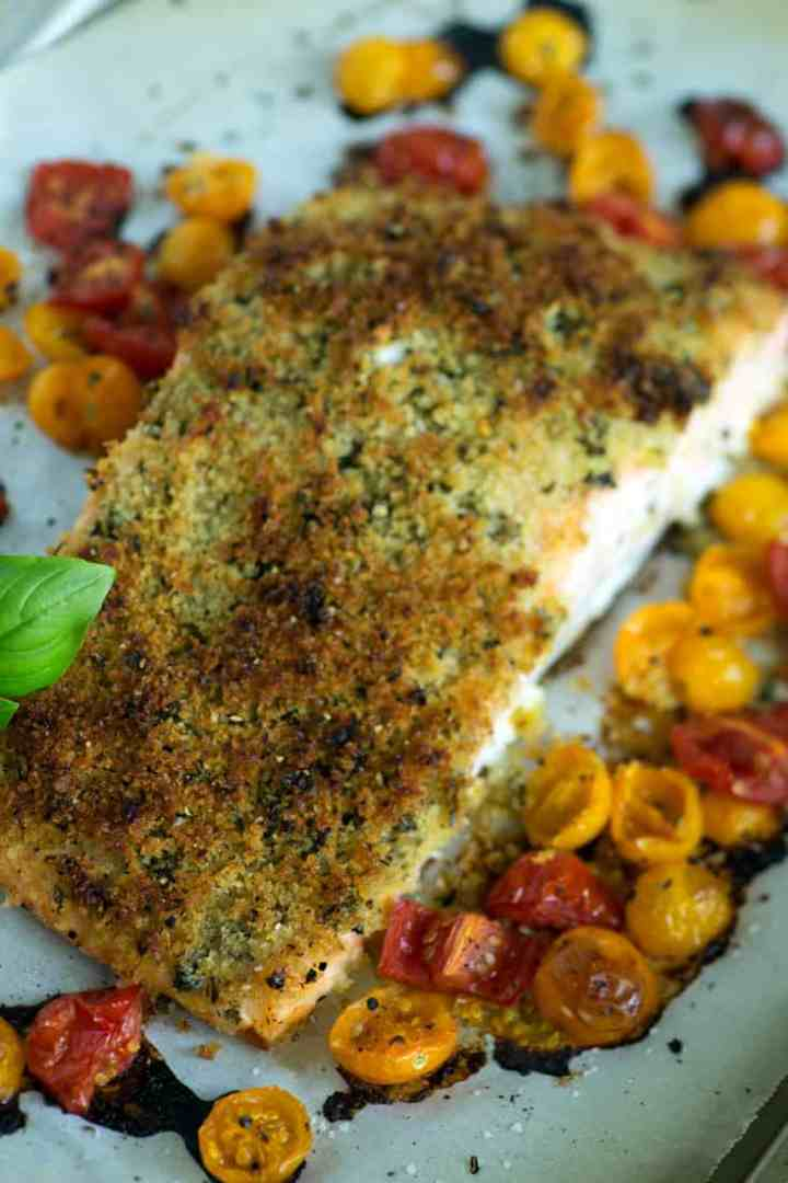 Herbed salmon on a baking sheet with cherry tomatoes