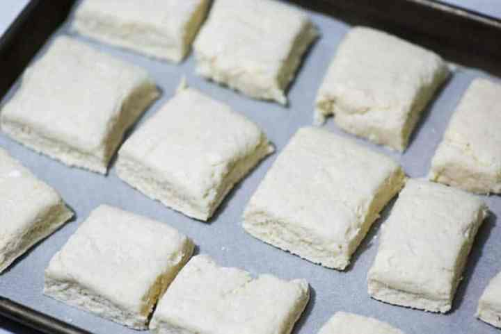 A cookie sheet with square biscuit dough