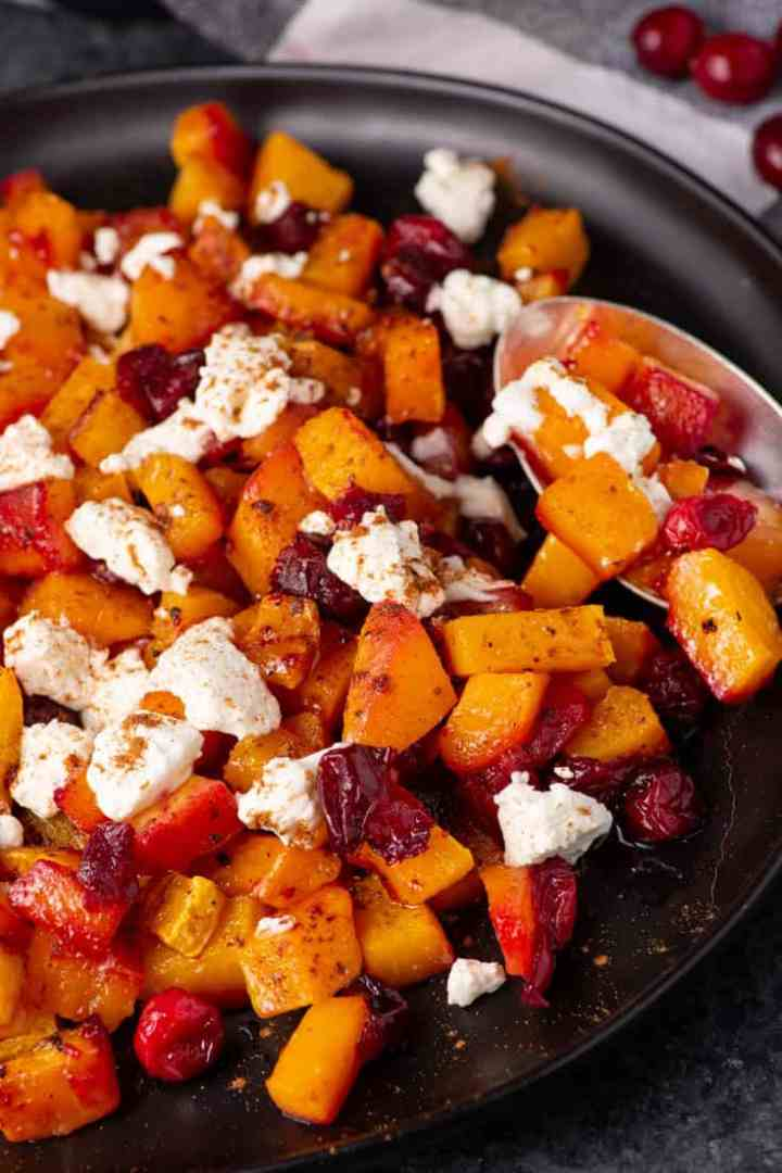 A spoon scooping out a serving of butternut squash with cranberries