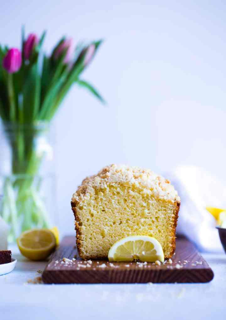 lemon loaf on wooden board with tulips in the background