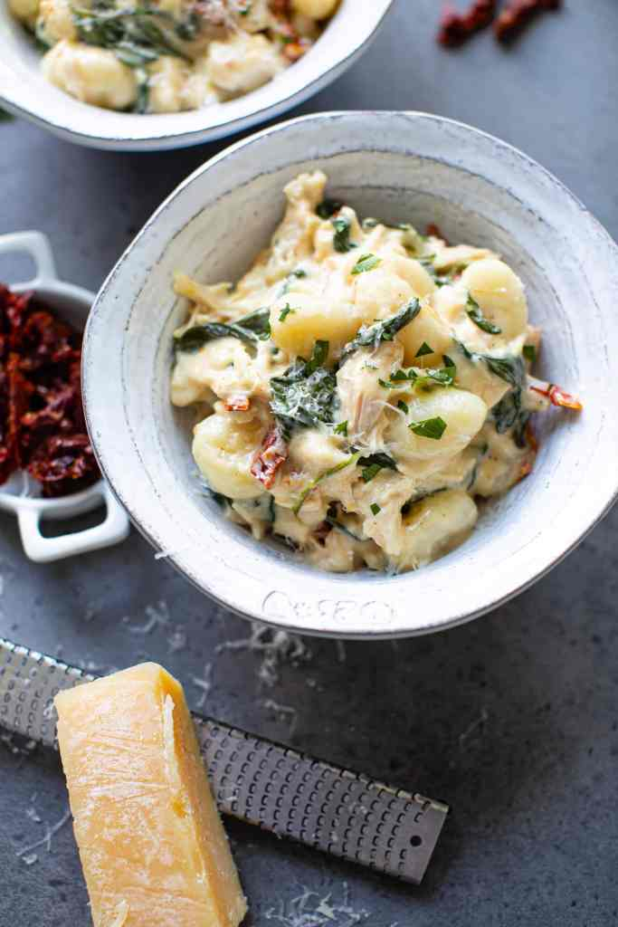 creamy chicken parmesan gnocchi in a white bowl
