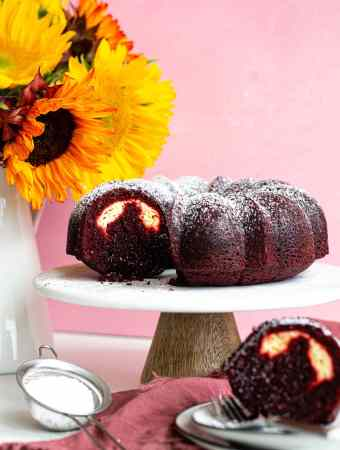 red velvet bundt cake on cake stand with flowers