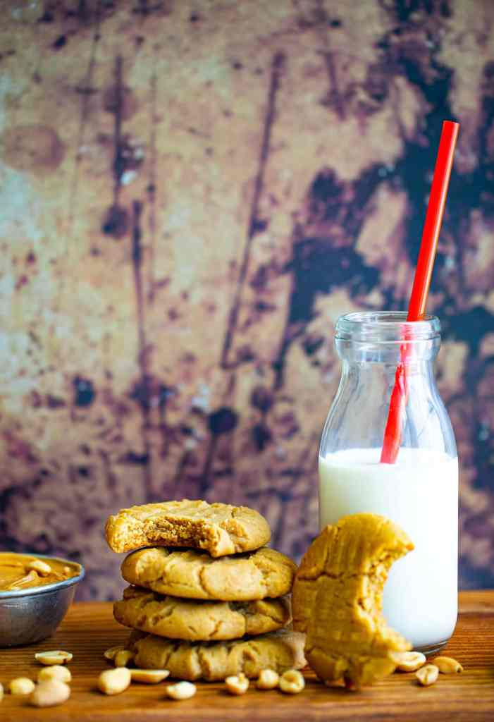 cookies stacked on top of each other with a glass of milk and red straw