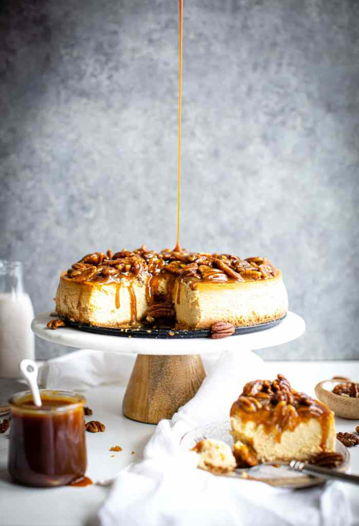 drizzle of caramel being poured onto a cheesecake