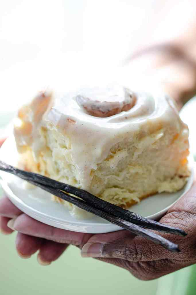 black woman's hands holding a big cinnamon roll on a small white plate