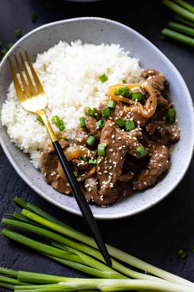 beef and rice in a gray speckled bowl with gold fork