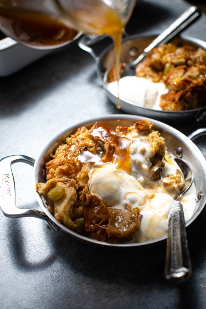 challah bread pudding with hand pouring bourbon sauce