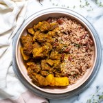 curry goat and rice and peas in pink bowl with linen