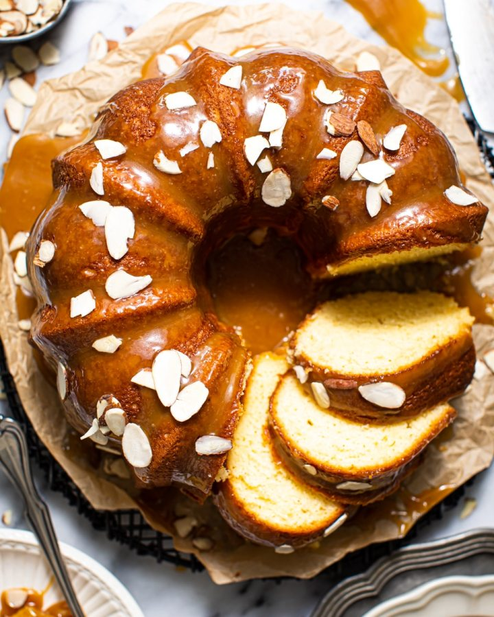 almond bundt cake with caramel icing on marble surface
