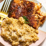 baked cajun salmon with parmesan risotto on pink and white plate