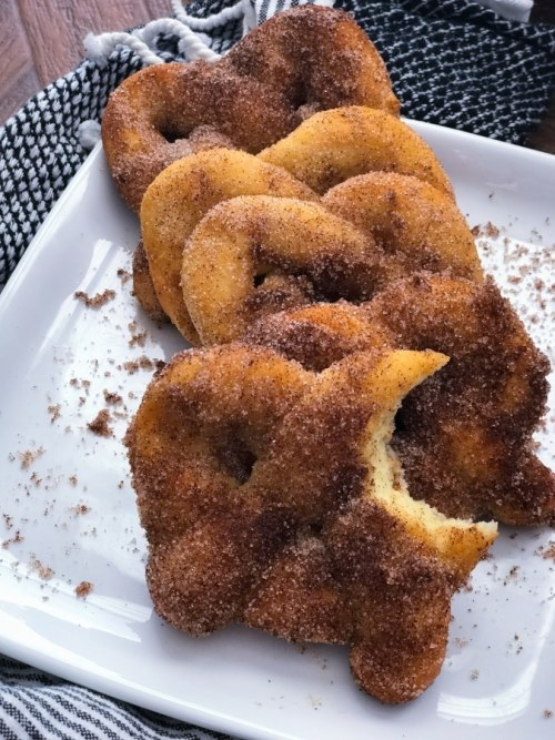 cinnamon sugar pretzels lined up together on a plate with one bitten into