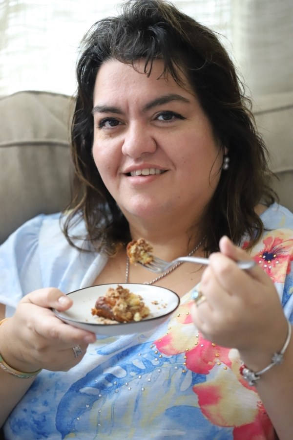 photo of my mom eating a piece a piece of coffee cake with a fork held up to her mouth