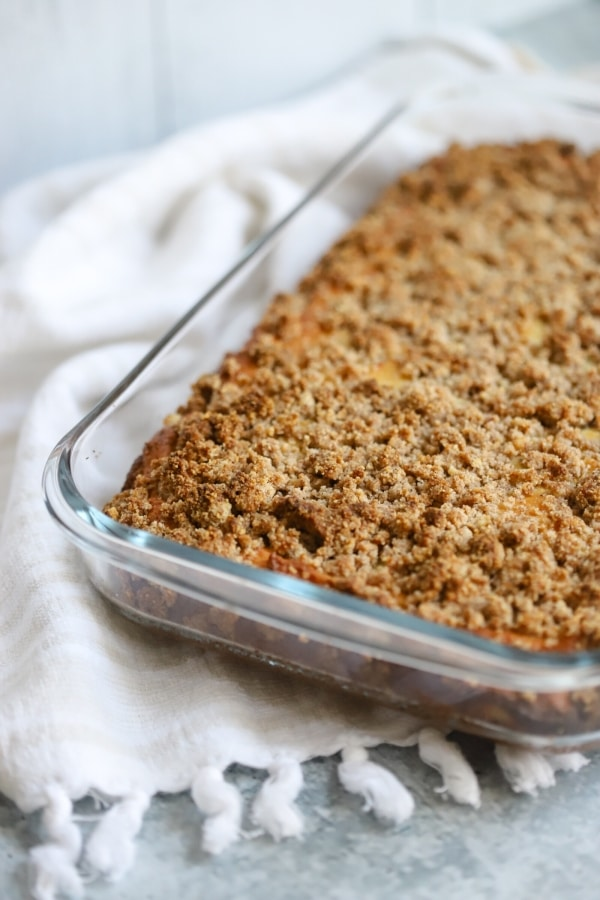 coffee cake fresh out the oven in a small baking glass dish. up close view of the cinnamon crumble