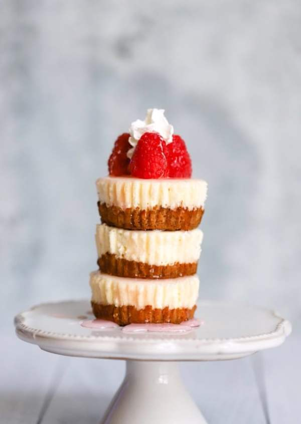 three mini cheesecake stacked up on each other with raspberries and whipped cream on top