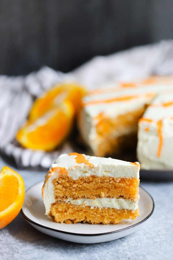 a single slice of orange creamsicle cake with the rest of the cake in the background