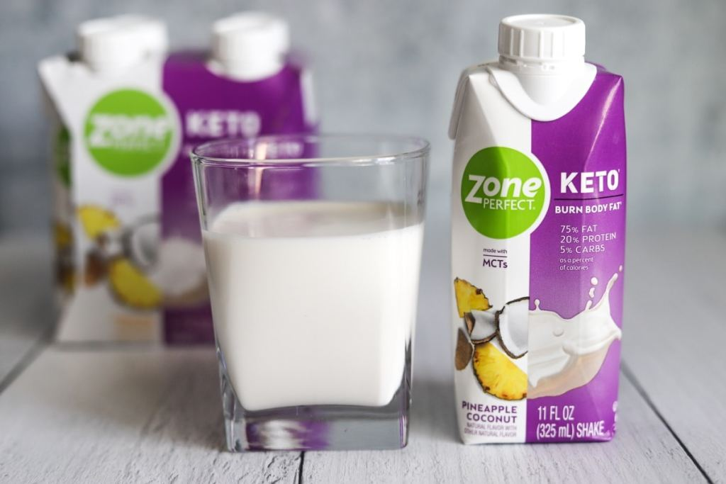 photo of a glass of ZonePerfect pineapple coconut keto shake with the package next to it and box behind the glass