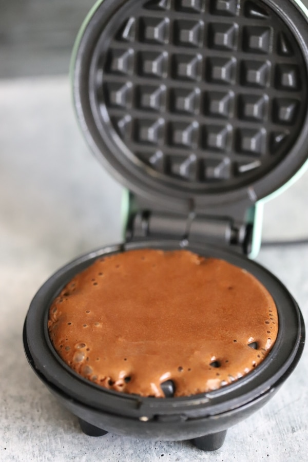 poured batter beginning to cook on waffle skillet
