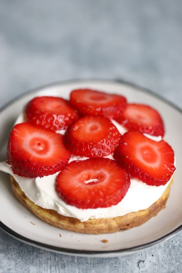 chaffle with whipped cream and strawberries on top, creating the middle layer