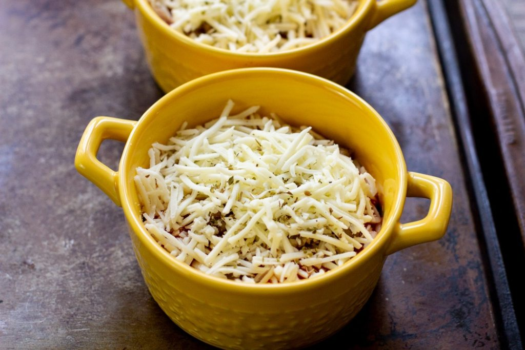 lasagna bowls topped with shredded cheese ready to go in the oven