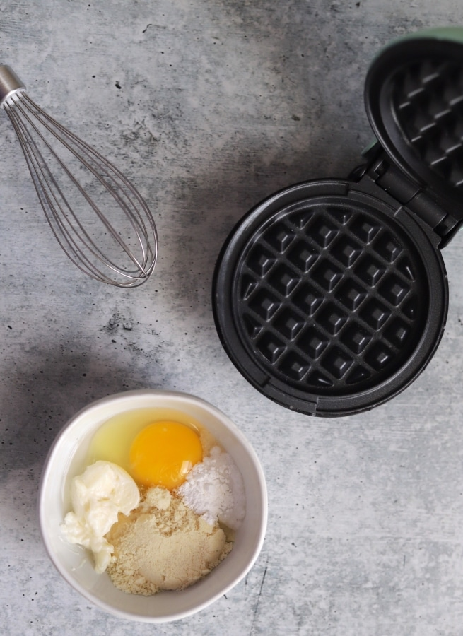top view shot of ingredients in a bowl, mini waffle maker, and a whisk