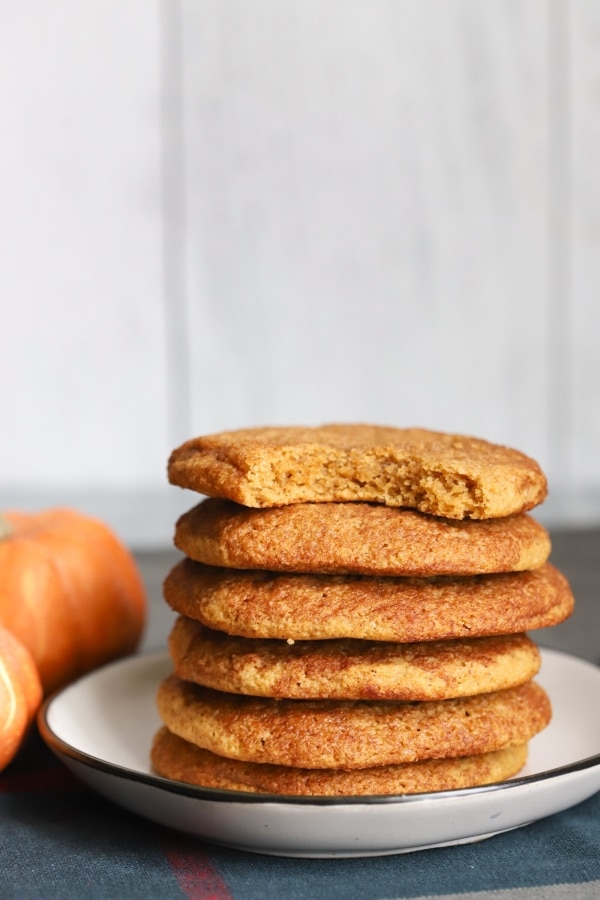 a stack of keto pumpkin snickerdoodle cookies that have a bite taken out of the first one on top