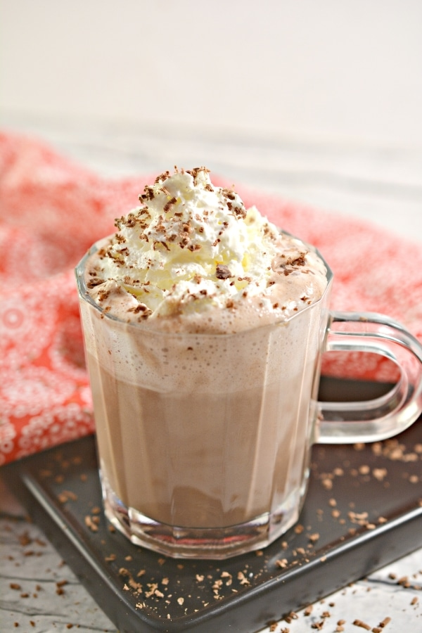 hot chocolate with whipped cream in a cup on top of a plate