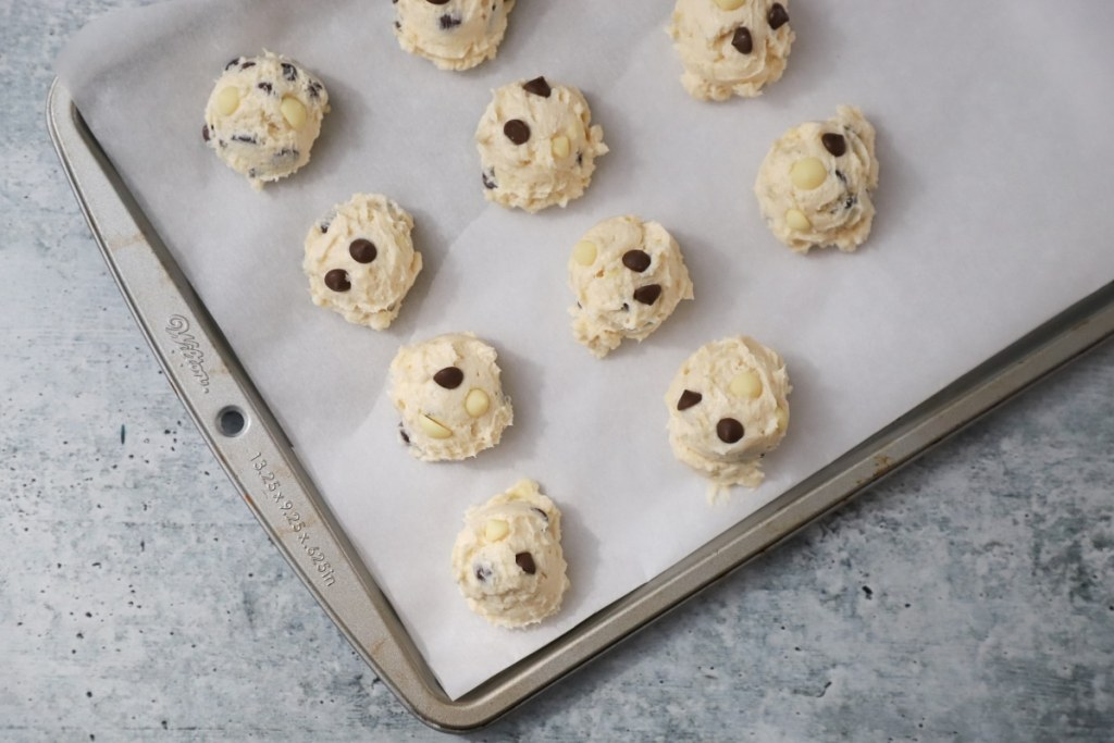 scooped cookie dough a parchment paper lined baking pan