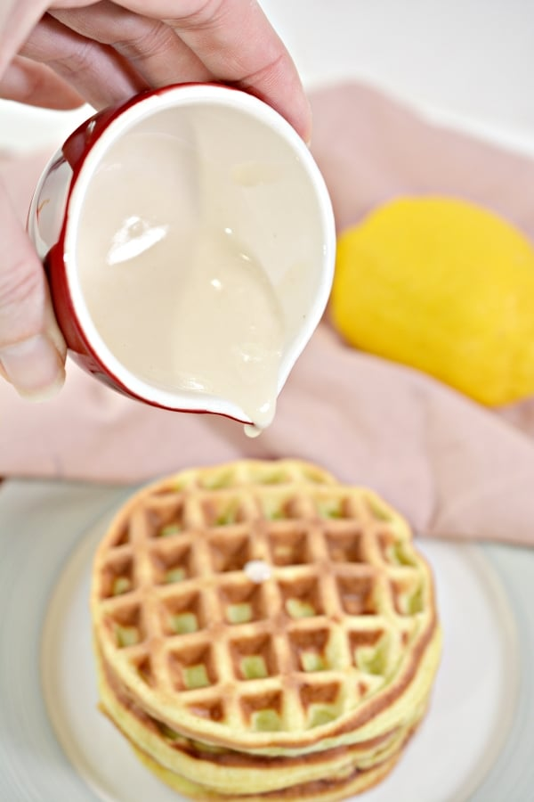 lemon glaze being poured on top of a stack of lemon chaffles