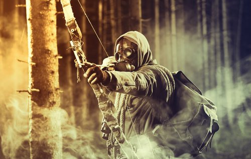 A male bow hunter wearing gas mask, draws back on his bow
