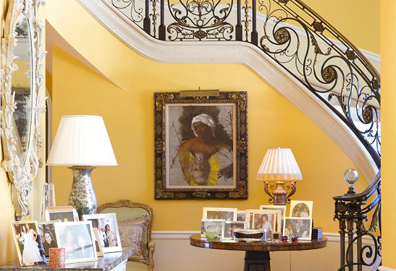 Oprah's entrance includes a yellow staircase with a painting and personal photos displayed.
