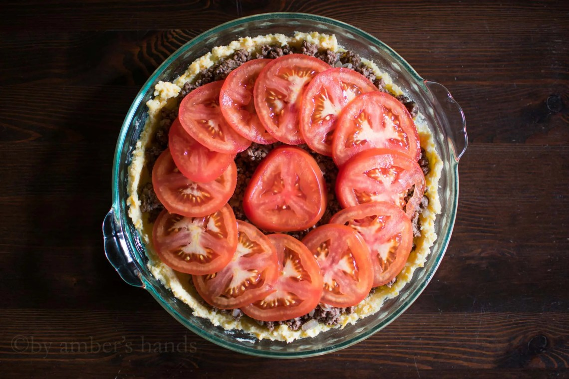 Crust layered with meat mixture and tomatoes