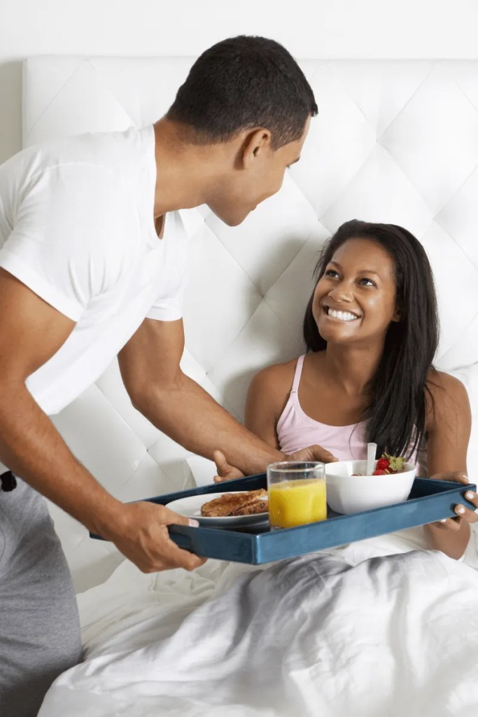 Man serving breakfast in bed to woman