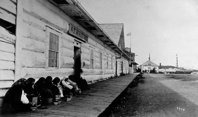 Crowd huddled next to building in Sitka, Alaska, circa 1890.