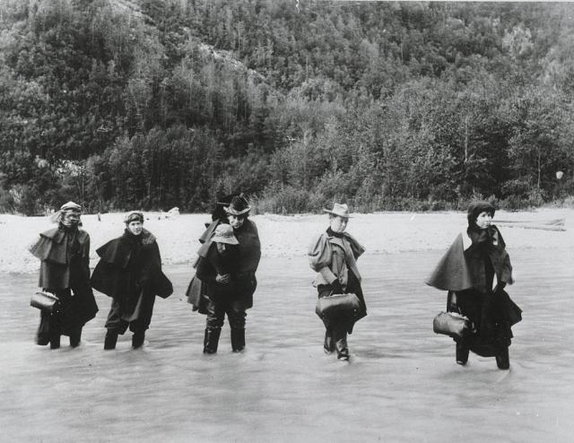A man carries an actress across an Alaskan river while others must ford it to get to a gold mine, 1897.