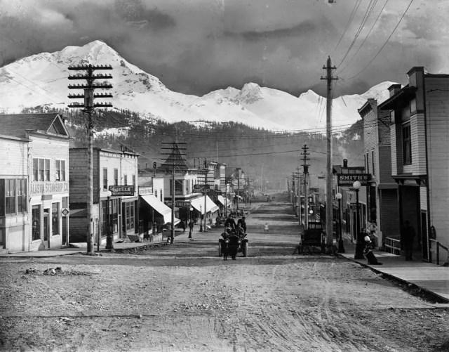 A main street in Cordova, Alaska, with utility poles, boardwalks, and light traffic, 1868.