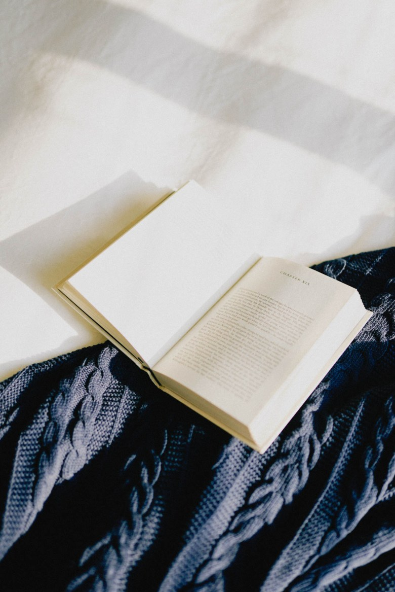 book on white bedding and navy cable knit blanket