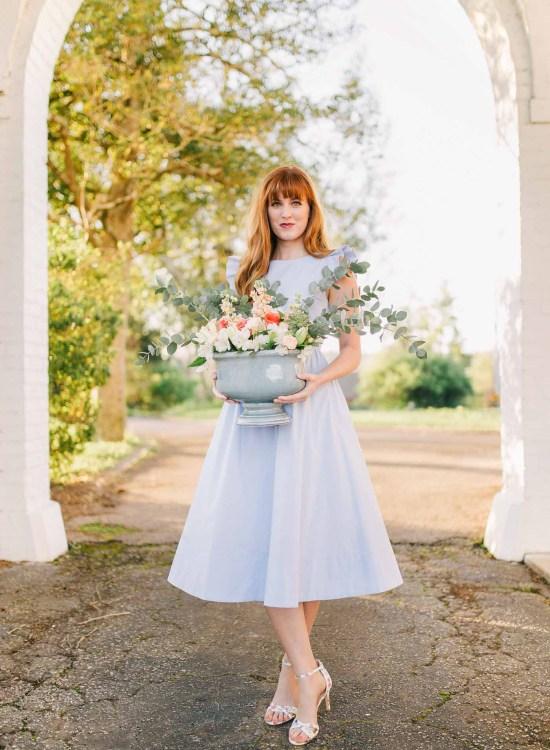 Spring floral arrangement with blue vase, eucalyptus, white stock, peach roses