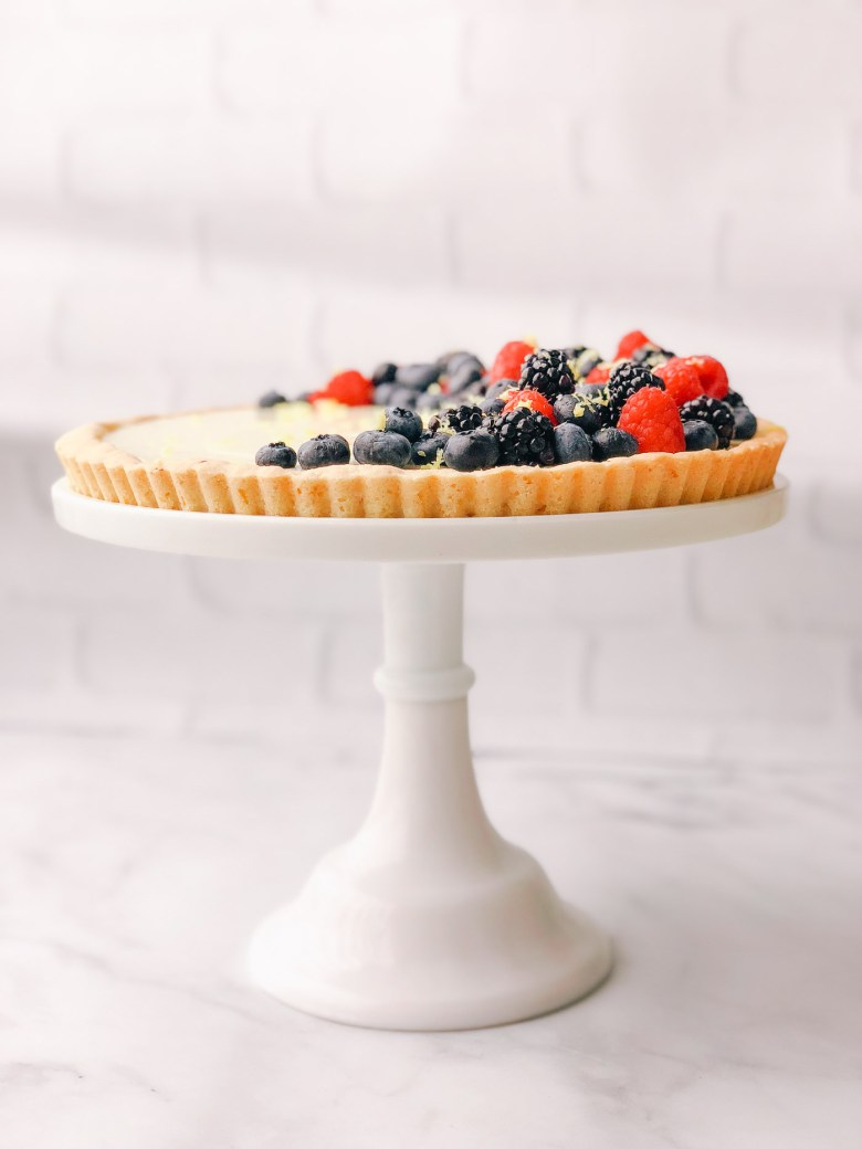 Lemon honey tart topped with mixed berries on a tall white cake stand in a crisp white kitchen.