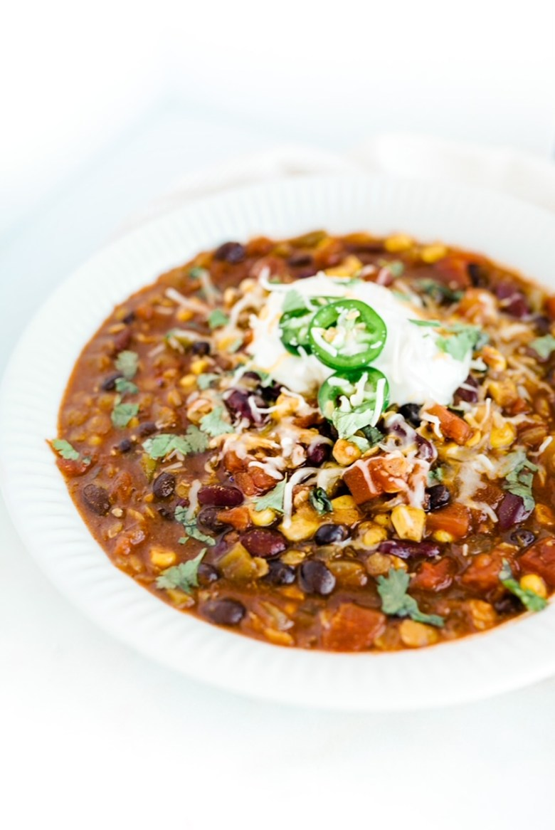 lentil veggie chili topped with sour cream, cheese, and jalapeños in white bowl on white marble counter