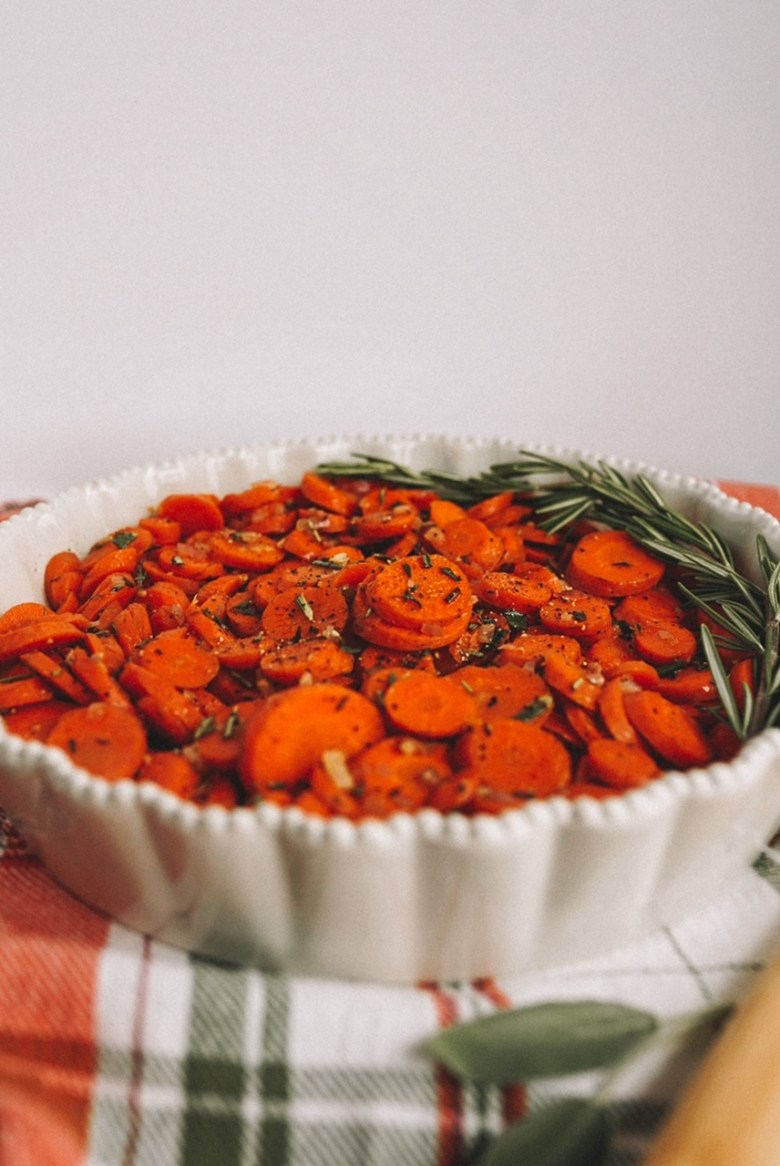 sliced carrots with herbs in round cream baking dish on green and orange plaid dish towel