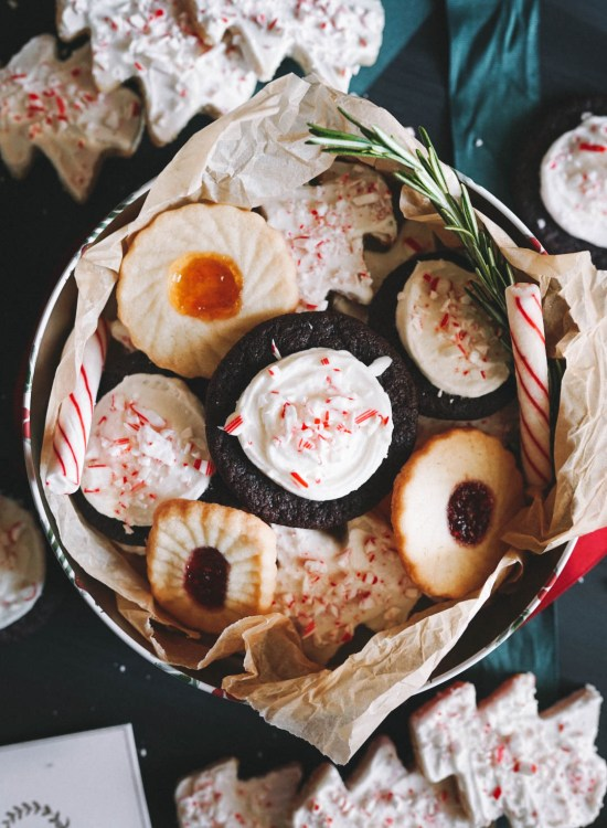 A mix of christmas cookies in a round tin on a black backdrop with wrapping ribbons surrounding