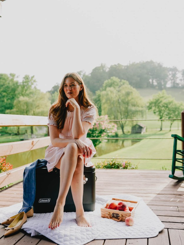 girl in peach gingham dress sitting on cooler on cabin porch in the mountains