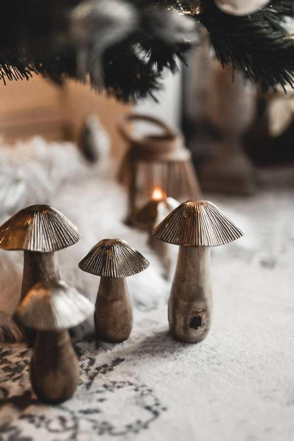Champignons en bois et laiton au pied du sapin pour une décoration Noël nature