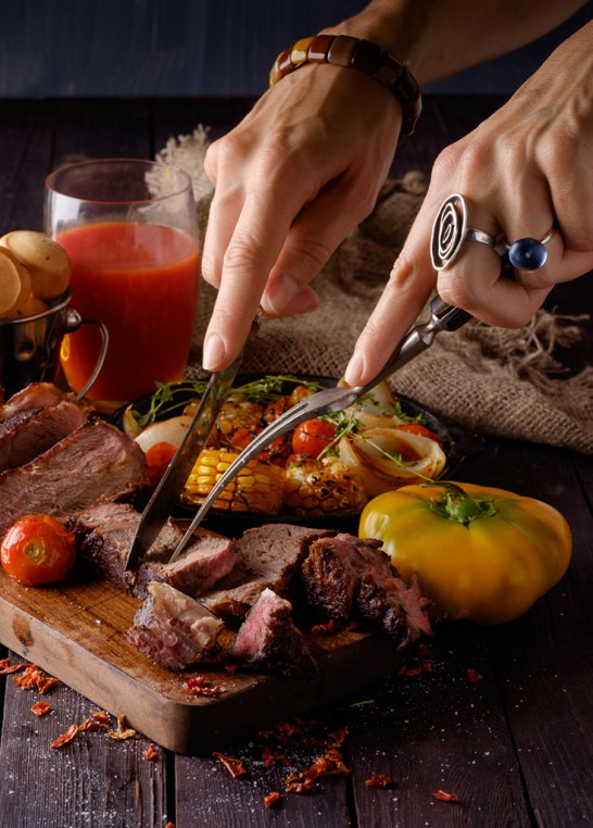 Grilled steak sliced on a cutting board. Entrecote with vegetables on a wooden background. Woman slicing a grilled beef stead.