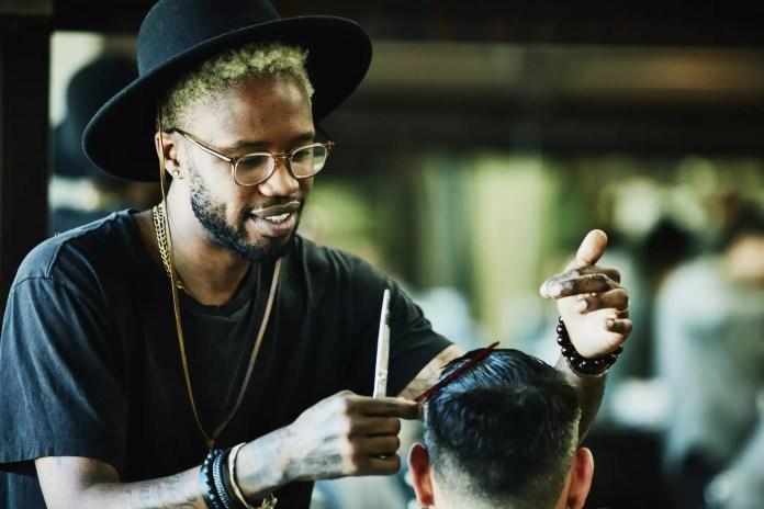Black barber cutting a man's hair