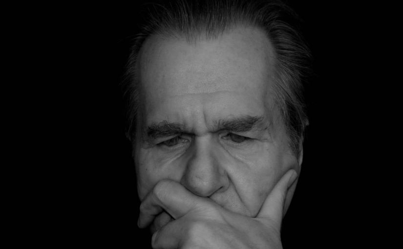A picture of a man reasoning reflectively. His brow is furrowed and he holding his head up with his hand.