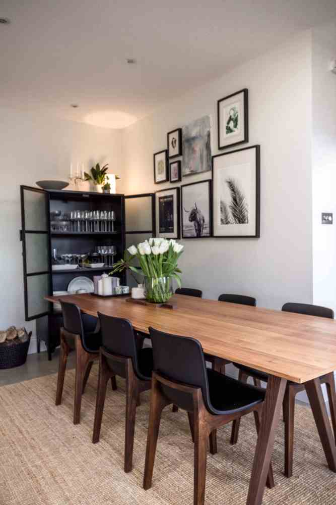 Kitchen diner with a table for 10 people. Black metal cabinet for crockery
