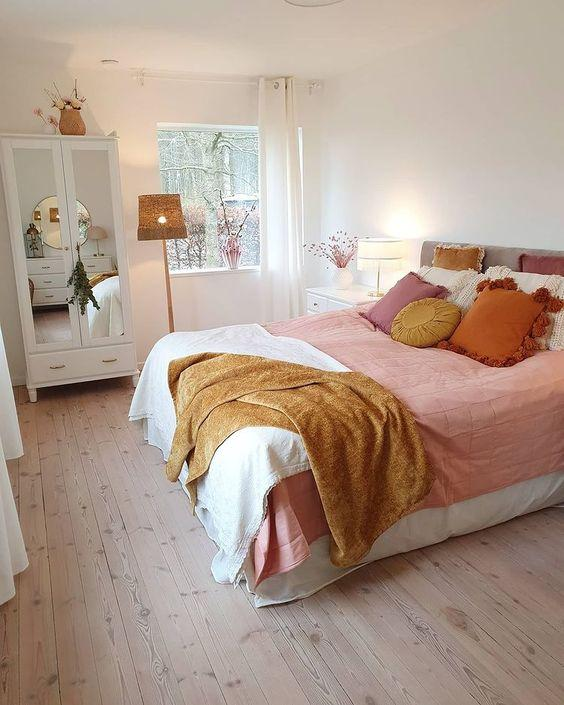 scandi style bedroom with wood flooring and pink and orange accessories